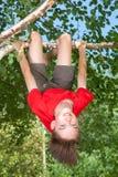 垂悬从一棵树的青少年的男孩在夏天庭院里 库存照片