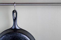 垂悬从勾子和标尺的老生铁煎锅 免版税库存图片