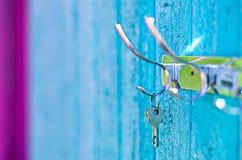 垂悬从在老被绘的木墙壁上的一个勾子的钥匙外面 免版税图库摄影