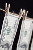 垂悬从在黑暗的背景的晒衣绳的一百元钞票 免版税库存照片