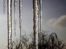 垂悬从屋顶的透明冰柱反对多云天空 库存照片