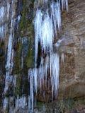 垂悬从山边的Icesicles 库存图片
