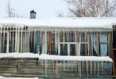 垂悬从房子屋顶的长的冰柱  库存图片