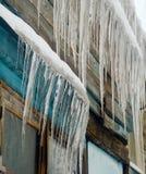 垂悬从房子屋顶的长的冰柱  免版税库存图片