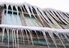 垂悬从房子屋顶的长的冰柱  库存照片