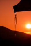 反射日落的冰柱 免版税库存图片