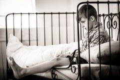 垂悬他的腿的哀伤的男孩在床边缘  免版税库存照片