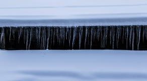 垂悬从积雪的瑞士山中的牧人小屋屋顶的icicicles行  图库摄影