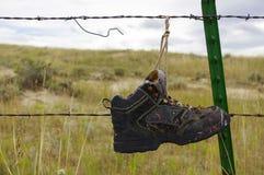 垂悬从铁丝网篱芭的老鞋子 免版税库存图片