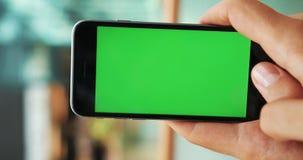 垂直的录影 人手在街道绿色屏幕大模型chromakey迷离背景中的拿着智能手机检查新闻 股票视频