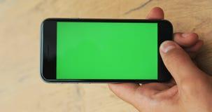 垂直的录影 供以人员手藏品和使用智能手机在街道绿色屏幕大模型chromakey迷离背景中 股票录像