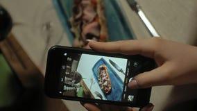 垂直的录影 垂直的录影 在电话的美丽的白肤金发的妇女照片食物 摄制食物 股票视频