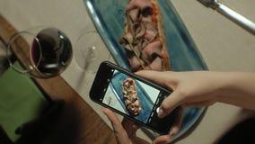 垂直的录影 垂直的录影 在电话的美丽的白肤金发的妇女照片食物 摄制食物 股票录像