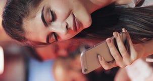 垂直的录影 有美好的微笑的年轻可爱的妇女在晚上使用智能手机 坐在酒吧的性感的女孩 股票录像