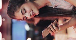 垂直的录影 有美好的微笑的年轻可爱的妇女在晚上使用智能手机 坐在酒吧的性感的女孩 影视素材