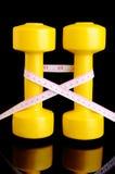 垂直在黑色安置的两把黄色哑铃和卷尺 库存照片