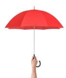 垂直拿着在白色背景的一只白色男性手一把开放红色伞 免版税库存图片