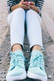 垂直构筑在牛仔裤和运动鞋的女性腿 免版税库存图片