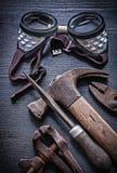 垂直的看法风镜锤子钳子在葡萄酒木头板锉 免版税图库摄影
