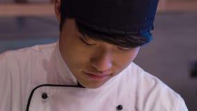 垂直的移动式摄影车射击了微笑的亚洲厨师切口 股票视频
