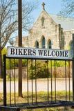 垂直:与自行车立场的教会标志:骑自行车的人欢迎 库存照片