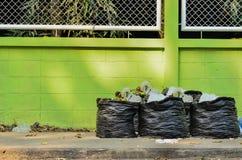 垃圾和waiste在黑袋子 免版税库存图片