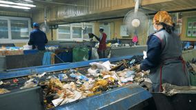 垃圾在传动机移动,而排序它的工作者在一个回收厂 影视素材
