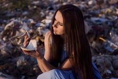 垃圾填埋的女孩拿着一个残破的杯子特写镜头的碎片 免版税库存照片