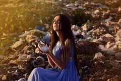 垃圾填埋的女孩拿着一个残破的杯子的碎片 免版税库存照片