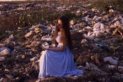 垃圾填埋的女孩拿着残破的杯子 免版税库存照片