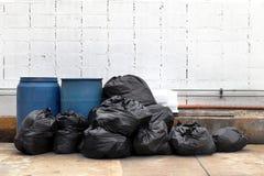 垃圾是堆全部在走道社区村庄倾销,许多垃圾塑料袋黑色废物,从垃圾塑料废物的污染 免版税库存照片