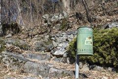 垃圾箱在有树和岩石的一个绿色公园 免版税库存图片
