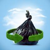 垃圾袋和绿色箭头从草 回收概念 免版税库存照片