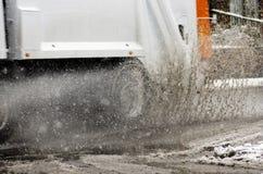 垃圾车在大水坑乘坐在多雪的天 雨夹雪飞溅 免版税库存图片