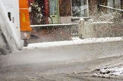 垃圾车在大水坑乘坐在多雪的天 雨夹雪飞溅 图库摄影