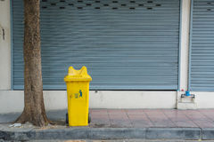 垃圾,回收和庭院废物的黄色自行车前轮离地平衡特技容器 在泰国脚道路路面的老垃圾桶 库存照片