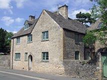 垫木的石砖房子在黄木樨草 免版税库存照片