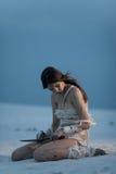 埃及妈咪的图象的女孩坐与刀子的沙子在她的h 免版税库存照片