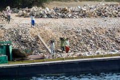埃及工作者在尼罗河的一艘驳船用手装载石头 免版税图库摄影