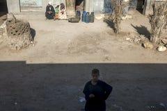 埃及男孩在开罗ourskirts的一列固定式火车旁边站立在埃及 图库摄影