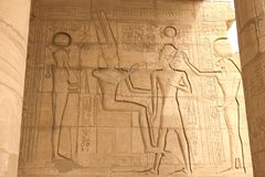 埃及象形文字和图画在墙壁和专栏上 埃及语言、古老神象形文字的生活和人们 库存照片