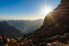埃及,西奈,登上摩西 从香客攀登摩西和黎明-与光芒的早晨太阳山在sk的路的看法 免版税库存照片