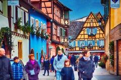 埃吉桑,阿尔萨斯,法国- 2017年12月24日:游人沿盛大云香街道走,在五颜六色的半木料半灰泥的房子中 免版税图库摄影