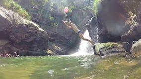 埃拉,斯里兰卡- 2014年3月:跳进河的人的慢动作在美丽的瀑布旁边 影视素材