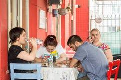 埃斯基谢希尔,土耳其- 2017年6月14日:小组乏味朋友在自助食堂、饮用水和茶,谈话坐电话 免版税库存图片