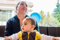 埃斯基谢希尔,土耳其- 2017年4月15日:坐在窗口前面的一张咖啡馆桌上的母亲和儿子 免版税库存照片