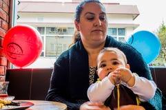 埃斯基谢希尔,土耳其- 2017年4月15日:坐在窗口前面的一张咖啡馆桌上的母亲和儿子 免版税库存图片