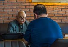 埃斯基谢希尔,土耳其- 2017年4月19日:有穿着衣服的镜片的老人坐在咖啡馆桌上 库存照片