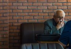埃斯基谢希尔,土耳其- 2017年4月19日:有穿着衣服的镜片的老人坐在咖啡馆桌上 免版税库存图片