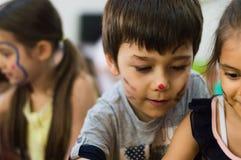 埃斯基谢希尔,土耳其- 2017年5月05日:有色的面孔的享用的小男孩是以他的朋友在幼儿园 库存照片